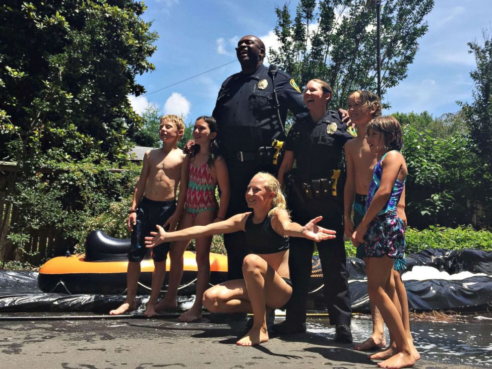 PHOTO: Children from the neighborhood pose with Asheville, North Carolina, police officers after riding down the slip n slide, July 2, 2017.
