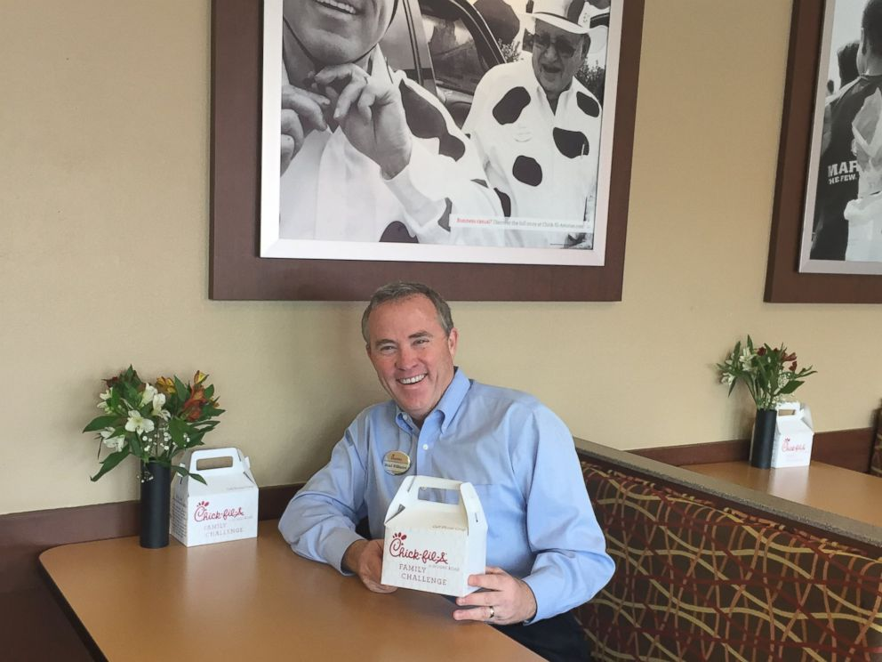 PHOTO: Chick-fil-A restaurant owner Brad Williams poses with one of the cell phone coops he created.