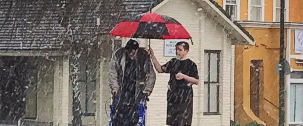 PHOTO: Elvis Ingersoll, 14, rushed out to hold an umbrella over the elderly mans head in Vallejo, California.