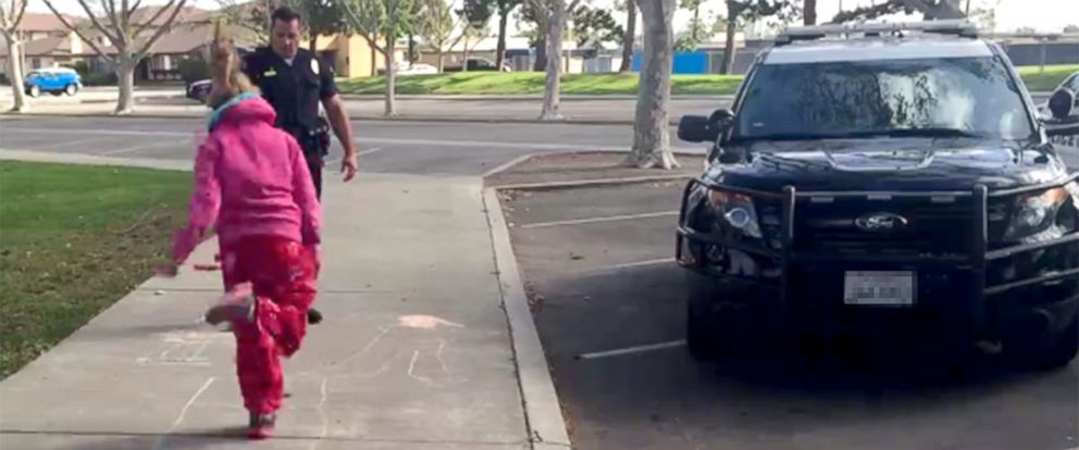 PHOTO: Officer Zach Pricer with the Huntington Beach Police Dept. showed an 11-year-old girl how to play hopscotch, March 30, 2016, while another officer worked on getting housing arrangements for the girl and her mother whod been living out of a car.