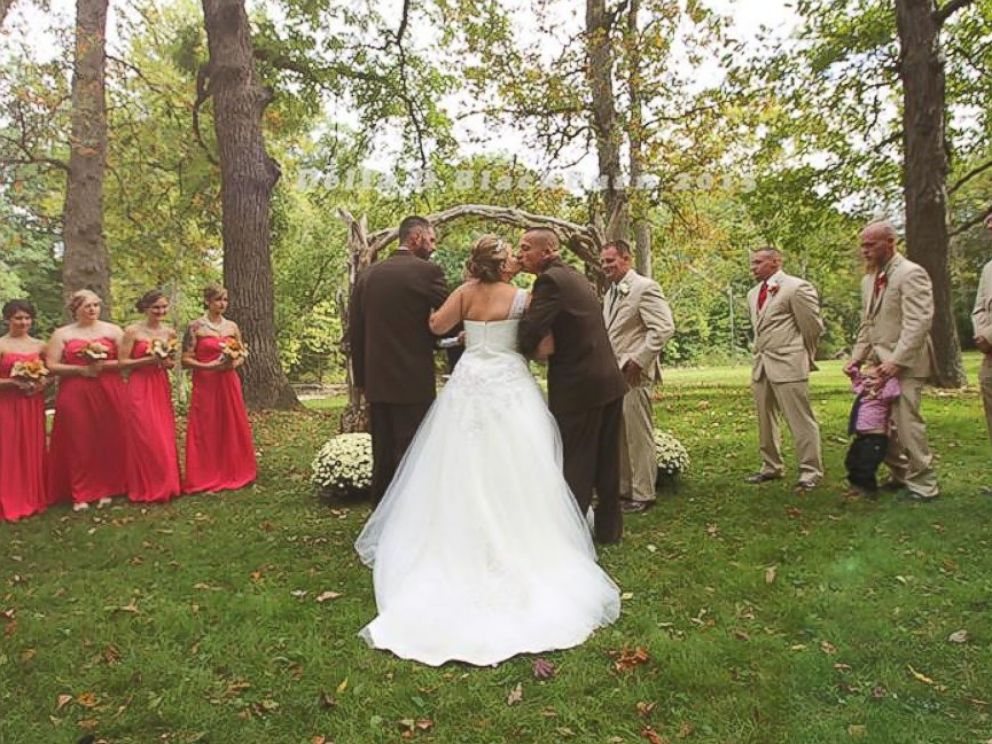 PHOTO: Brittany Pecks wedding photos have gone viral after her father grabbed her stepfather so they could both walk her down the aisle.