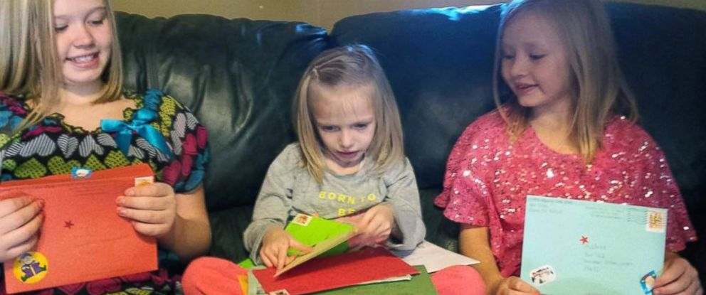 PHOTO: Addie Fausett, center, and her sisters Shaley Fausett, left, and Audree Fausett, right, open Christmas cards sent to them from strangers around the world.