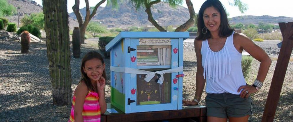 """PHOTO: Anna Wolcott, 6, photographed with her mother Heather on June 25 at the grand opening of her """"Little Free Library,"""" which was reported stolen by a neighbor on July 2."""
