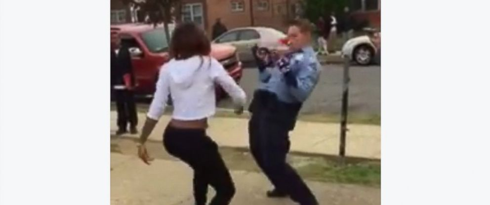 """PHOTO: Aaliyah Taylor, 17, dances off to """"Whip/Nae Nae"""" with a DC police officer who agreed to the challenge in order stop a conflict between two groups of teenagers."""