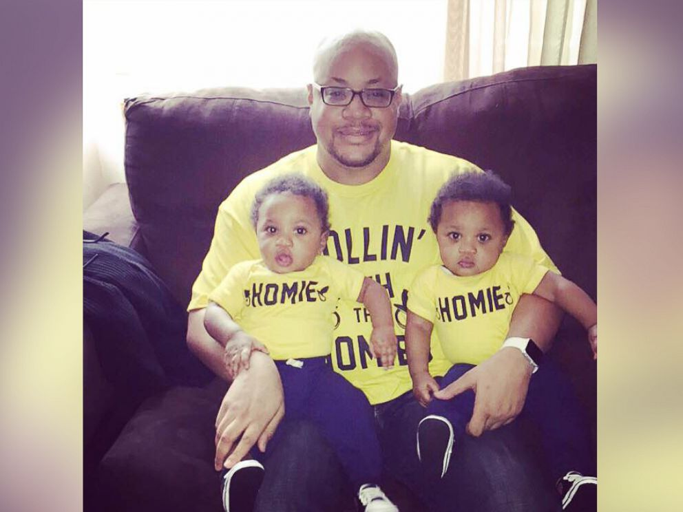 PHOTO: Kenny Moore, of Baltimore, Maryland, with his 12-month-old twins, Malcolm and Miles.