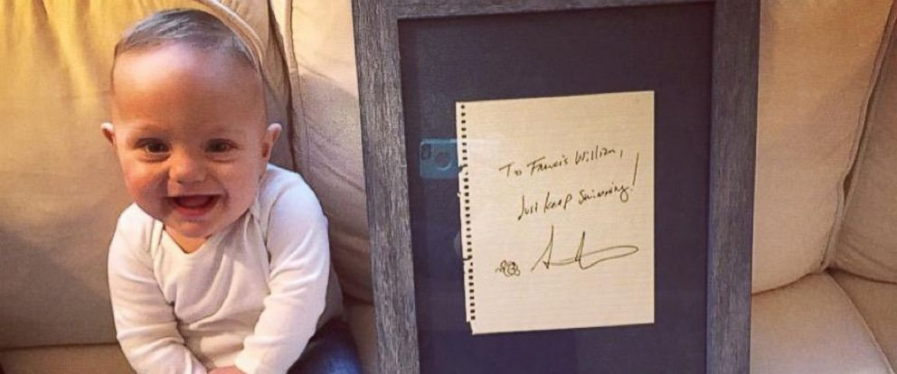 """PHOTO: Francis William Azize, 1, sits beside a note that reads """"Just Keep Swimming,"""" written by Andrew Stanton who created """"Finding Nemo and """"Finding Dory."""""""