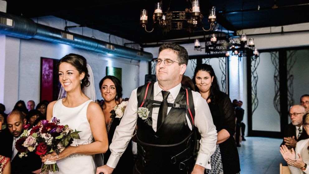 Scott Holland didn't let his multiple sclerosis stop him from walking his daughter, Elise Holland, down the aisle. He surprised her on her wedding day by using an exoskeleton to help him walk.