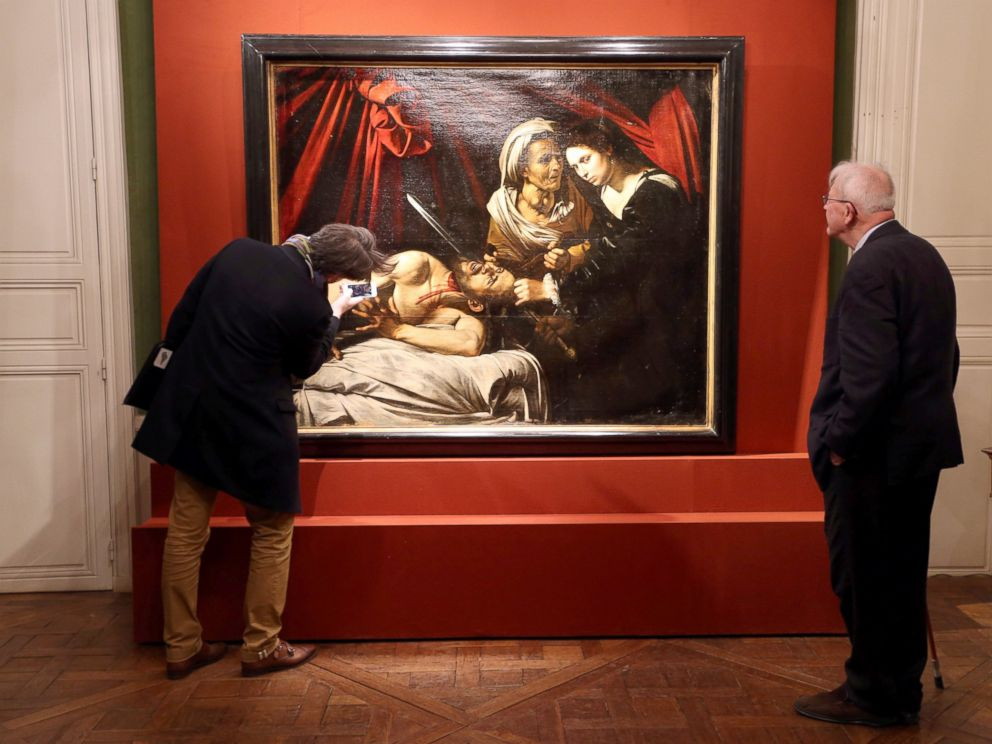 PHOTO: Visitors looks at a painting entitled Judith Beheading Holofernes during its presentation in Paris, April 12, 2016.
