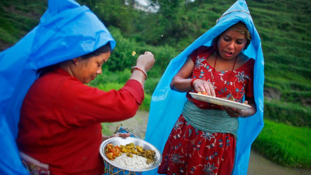 FILE - In this June 30, 2014 file photo, a farmer, left, ritualistically offers a small portion of food to god before eating her lunch while working at a rice field in Chunnikhel, Katmandu, Nepal. Languages evolve as societies develop and change, but the sounds we utter are also shaped, literally, by the placement of our jaw – and that is influenced by how we chew our food, researchers say in a report released Thursday, March 14, 2019, in the journal Science. (AP Photo/Niranjan Shrestha)
