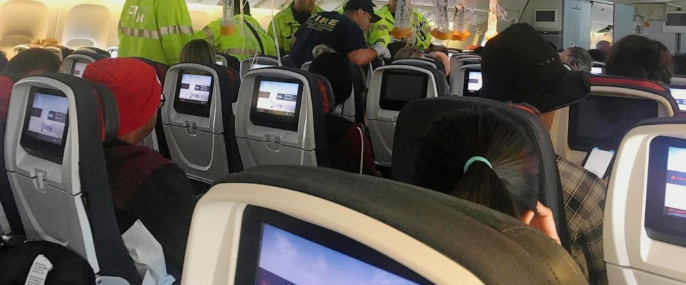 FILE - In this Thursday, July 11, 2019 photo provided by Tim Tricky of the band Hurricane Fall, emergency workers treat a passenger on an Air Canada flight to Australia that was diverted and landed at Daniel K. Inouye International Airport in Honolul