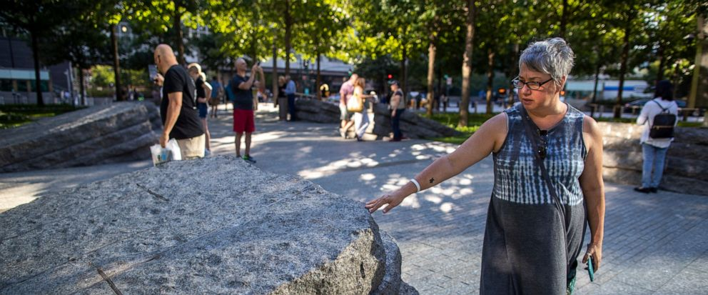 In this Thursday, Aug. 29, 2019, photo a visitor touches one of the granite slabs at the 9/11 Memorial Glade at the National September 11 Memorial & Museum in New York. When the names of nearly 3,000 Sept. 11 victims are read aloud Wednesday, Sept. 1