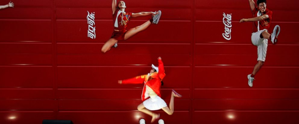 FILE - In this Aug. 20, 2008 file photo, a young girl mimics the pose of a Chinese Olympic athletes depicted in Coca-Cola advertising, at the Olympic green in Beijing. The International Life Science Institute, a group funded by the food industry, und
