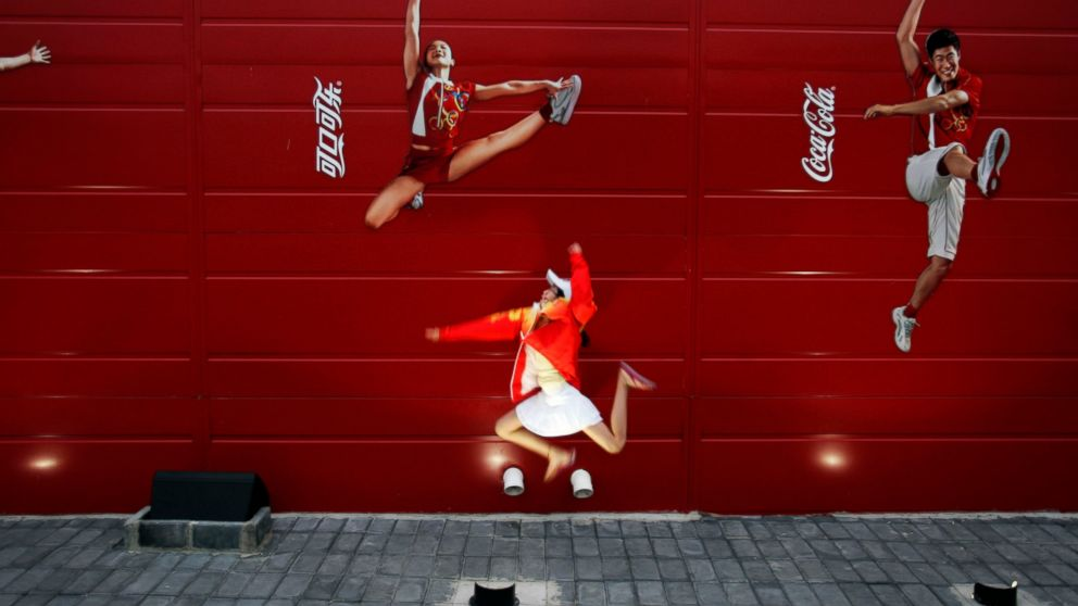 FILE - In this Aug. 20, 2008 file photo, a young girl mimics the pose of a Chinese Olympic athletes depicted in Coca-Cola advertising, at the Olympic green in Beijing. The International Life Science Institute, a group funded by the food industry, undermined China's efforts to keep obesity rates in check by overemphasizing the importance of physical activity rather than dietary restrictions, according to a new paper. The group sponsored obesity conferences on exercise science with speakers including Coke-funded researchers and a Coke executive. ILSI says it does not profess to have been perfect, but that it has adopted stricter guidelines. (AP Photo/Elizabeth Dalziel)
