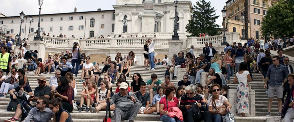 This combo picture shows the Spanish Steps in Rome, on Sept. 23, 2016, top, and Wednesday, Aug. 7, 2019, the day after the municipality decision to start the enforcement of a law designed to protect monuments and landmarks and are forbidding people f
