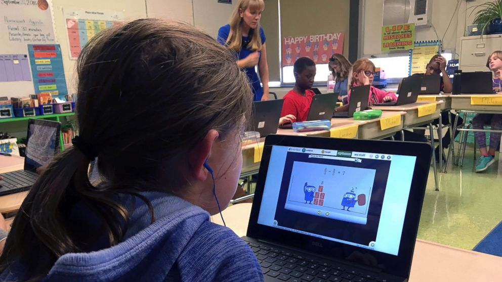 In this Sept. 20, 2018 photo, fifth grade student Ashlynn De Filippis, left, works math problems on the DreamBox system as teacher Heather Dalton, center rear, works with other students in class at Charles Barnum Elementary School in Groton, Conn. A wide array of apps, websites and software used in schools borrow elements from video games to help teachers connect with students living technology-infused lives. (AP Photo/Michael Melia)