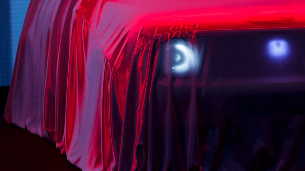 The new Honda 'E' concept car is veiled with a red dustsheet during the press day at the '89th Geneva International Motor Show' in Geneva, Switzerland, Tuesday, March 05, 2019. The 'Geneva International Motor Show' takes place in Switzerland from March 7 until March 17, 2019. Automakers are rolling out new electric and hybrid models at the show as they get ready to meet tougher emissions requirements in Europe - while not forgetting the profitable and popular SUVs and SUV-like crossovers. (Cyril Zingaro/Keystone via AP)
