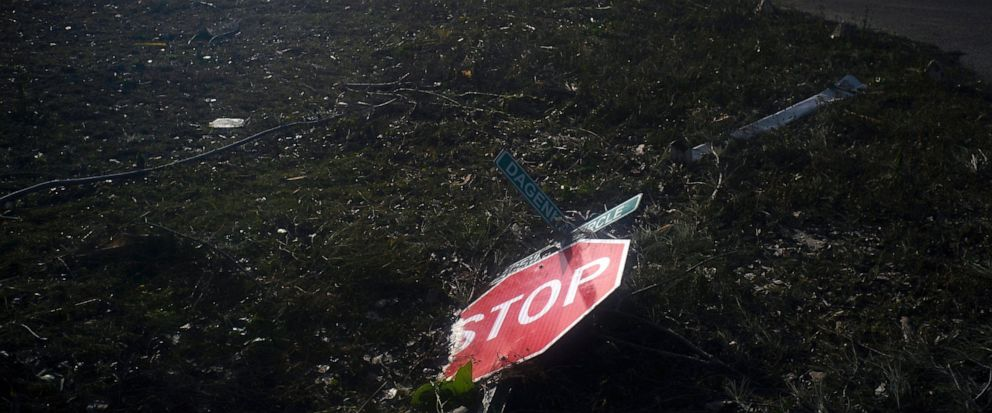 A traffic sign blown over by Hurricane Dorian lies on the ground in Pine Bay, near Freeport, Bahamas, Wednesday, Sept. 4, 2019. Rescuers trying to reach drenched and stunned victims in the Bahamas fanned out across a blasted landscape of smashed and