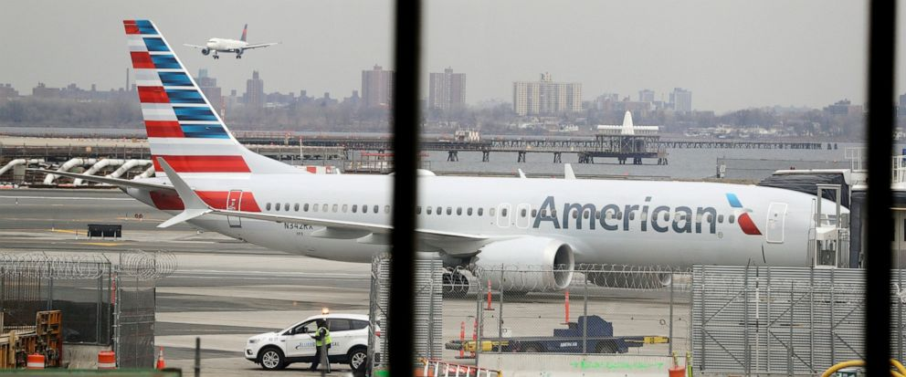 FILE - In a March 13, 2019 file photo, an American Airlines Boeing 737 MAX 8 sits at a boarding gate at LaGuardia Airport in New York. American Airlines is canceling 115 flights per day through mid-August because of ongoing problems with the Boeing 7