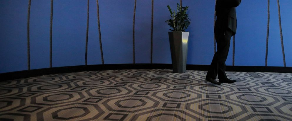 FILE - In this May 4, 2018, file photo a man talks on the phone in a hallway adorned with the palm tree-printed wallpaper at a hotel near the Los Angeles International Airport in Los Angeles. U.S. regulators are proposing new measures intended to thw