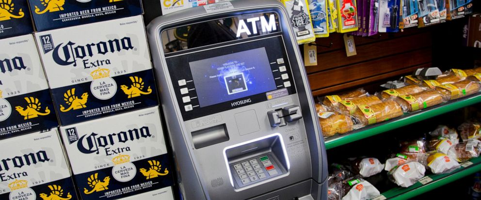 FILE - In this April 18, 2018, file photo, an ATM machine is in use at a New York convenience store. If you find yourself short on cash while on vacation, it might seem easiest to hit up the nearest ATM. But if that handy machine is not in your bank'