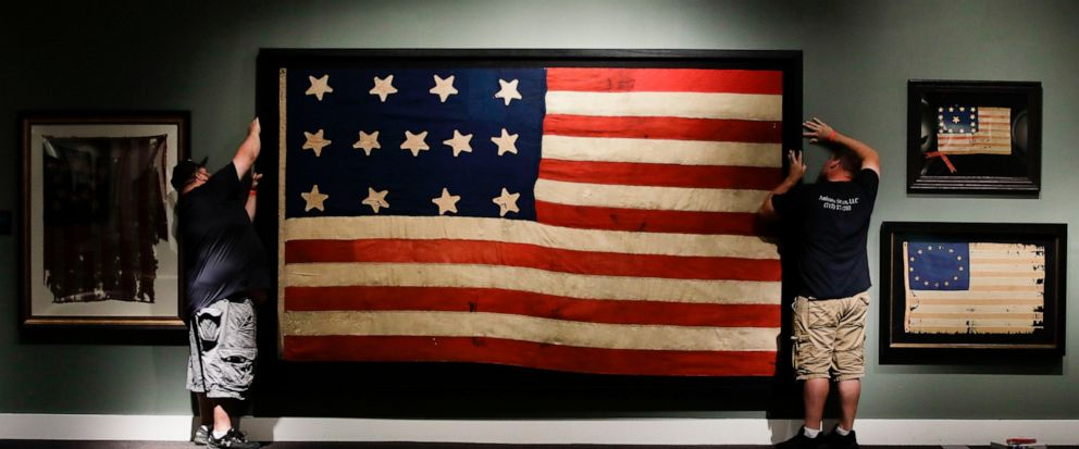 """In this Wednesday, June 12, 2019 photo, workmen hang a Federal Era flag as part of the new exhibit """"A New Constellation: A Collection of Historic 13-Star Flags,"""" at the Museum of the American Revolution in Philadelphia. The exhibit featuring 40 rare,"""