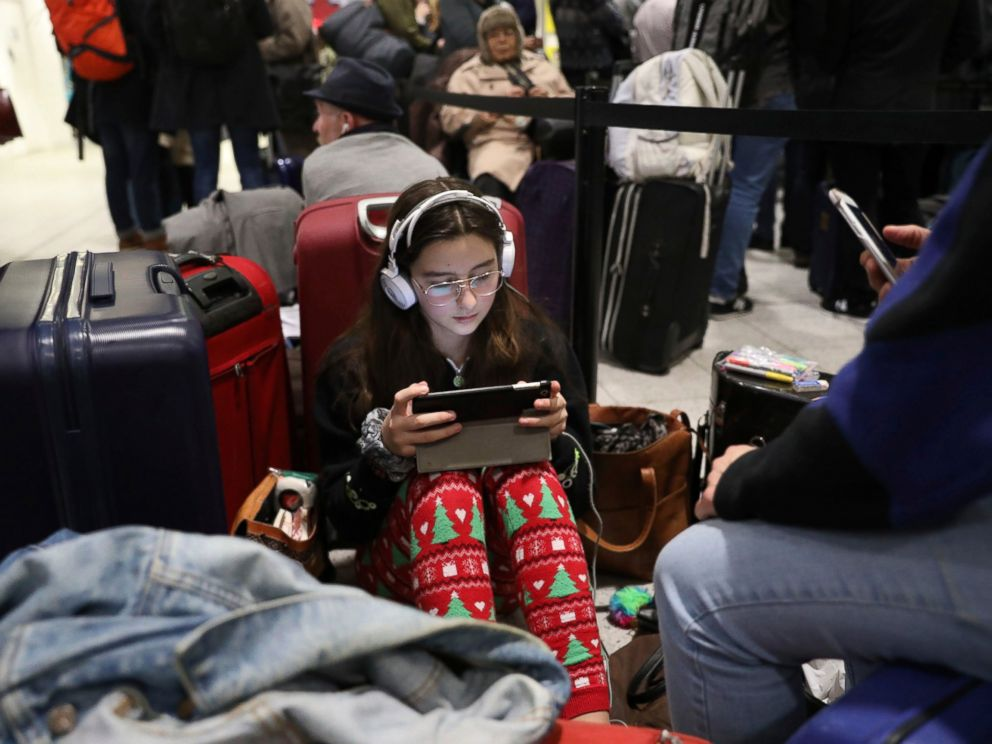 Passengers at Gatwick airport settle down to wait for their flights following the delays and cancellations brought on by drone sightings near the airfield, in London, Friday Dec. 21, 2018. New drone sightings Friday caused fresh chaos for holiday tra