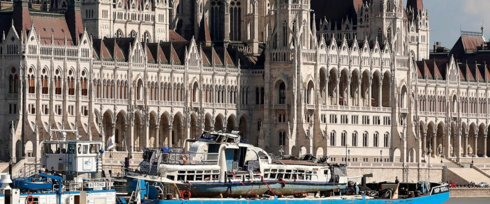 A barge carries the sightseeing boat past the house of parliament on the Danube river after it was lifted from riverbed in Budapest, Hungary, Tuesday, June 11, 2019. Four people are still missing from the May 29 collision between the Hableany (Mermai