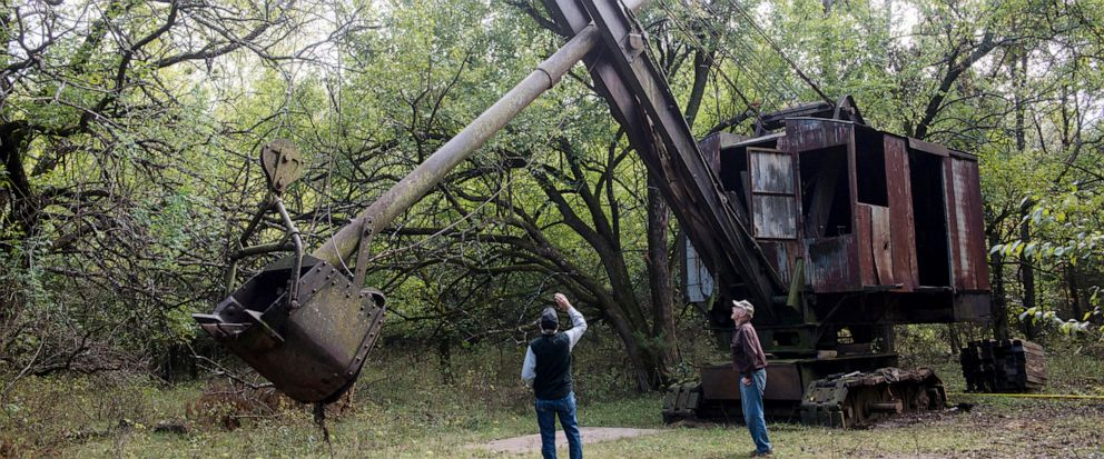 FILE--In this Oct. 16, 2018 file photo, Jim Lovell, left, and Carmen Boccia look over the Markley shovel where it has been for 70 years in nearby Cherokee, Kan. The historic coal mining shovel that was hidden under bramble for more than 70 years has