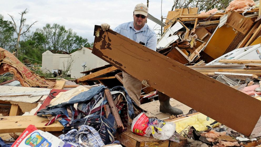 Roman Brown moves part of a wall out of his way as he looks for a friends medicine in their destroyed home along Seely Drive outside of Hamilton, Miss. after a storm moved through the area on Sunday, April 14, 2019. (AP Photo/Jim Lytle)