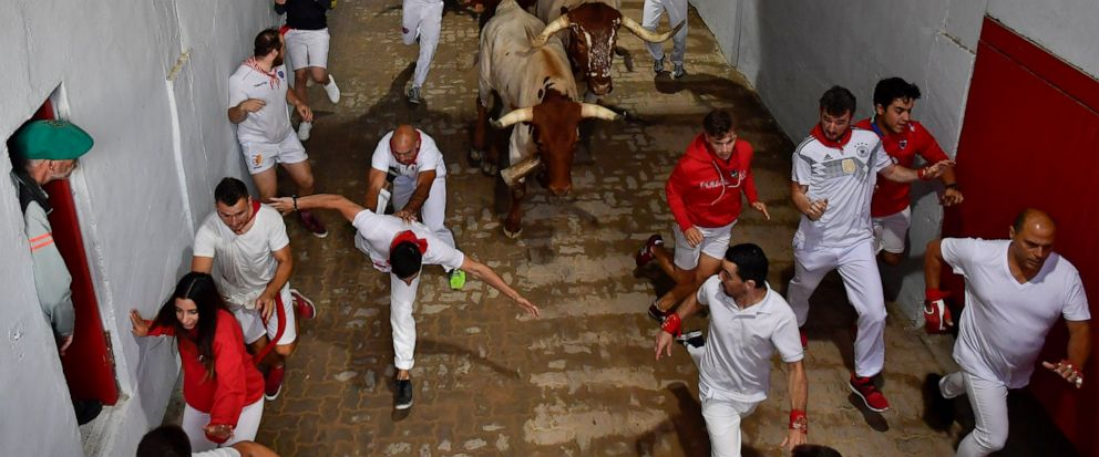 """Revellers run next to fighting bulls during the running of the bulls at the San Fermin Festival, in Pamplona, northern Spain, Sunday, July 14, 2019. The San Fermin fiesta made internationally famous by Ernest Hemingway in his novel """"The Sun Also Rise"""