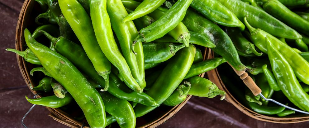 FILE - In this Aug. 9, 2017, file photo, fresh green chile awaits being roasted at Los Chile Bros, a stand outside Big Lots in Santa Fe, N.M. The long-simmering battle between New Mexico and Colorado over which state grows the best chile is heating u