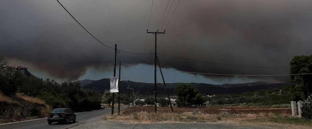 A cloud of smoke rises from a nearby forest fire at Psachna village on the island of Evia, northeast of Athens, Tuesday, Aug. 13, 2019. Dozens of firefighters backed by water-dropping aircraft are battling a wildfire on the island that has left the G