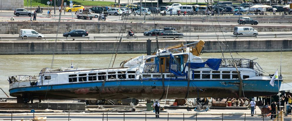 A crane places the wreckage of the sightseeing boat on a transporting barge at Margaret Bridge, the scene of the fatal boat accident in Budapest, Hungary, Tuesday, June 11, 2019. The Hableany sightseeing boat carrying 33 South Korean tourists and two