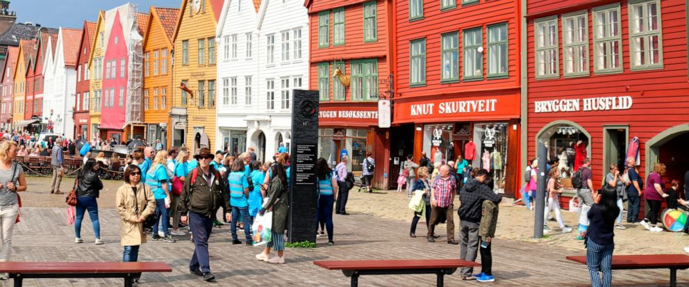 This June 6, 2019 photo shows people walking by the historic buildings of Bryggen, the old wharf area of Bergen, Norway. A trip on a cruise ship in spring and summer provides a close view of the high cliffs that tower over the narrow inlets. Unlike c