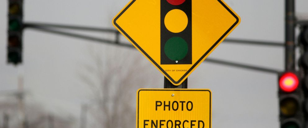 FILE - In this Tuesday, Feb. 10, 2015 file photo, a sign warns motorists of the presence of a red light camera in Chicago. Texas Gov. Greg Abbott signed a law Saturday, June 1, 2019 that bans red-light traffic cameras in Texas. (AP Photo/M. Spencer G