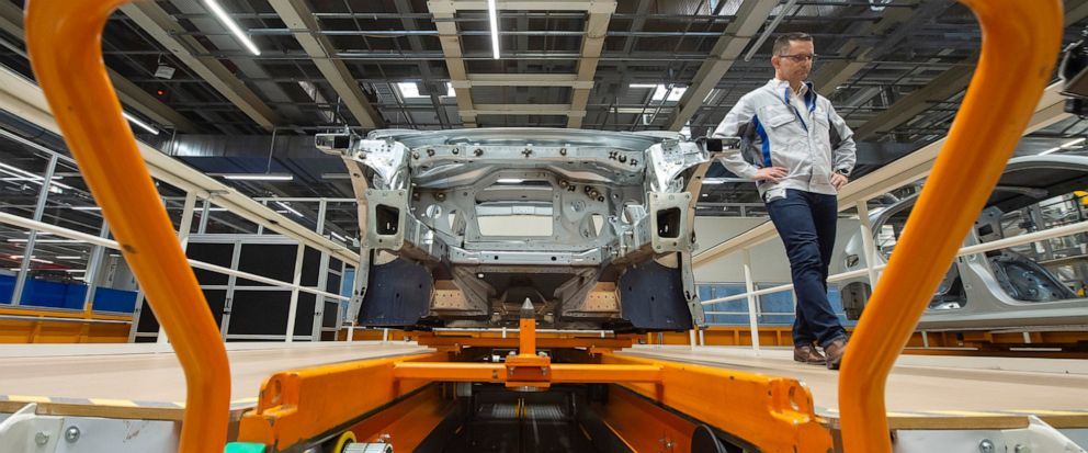 FILE - In this Tuesday, May 14, 2019 file photo, Heiko Roesch, head of body construction, walks besides the new electric ID.3 car body during a press tour at the plant of the German manufacturer Volkswagen AG (VW) in Zwickau, Germany. Volkswagen is