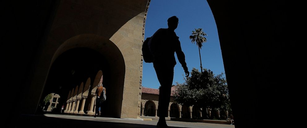 FILE - In this April 9, 2019, file photo, pedestrians walk on the campus at Stanford University in Stanford, Calif. College students who earned money this summer can make the most of it by including a few longer-term financial goals in their budgetin