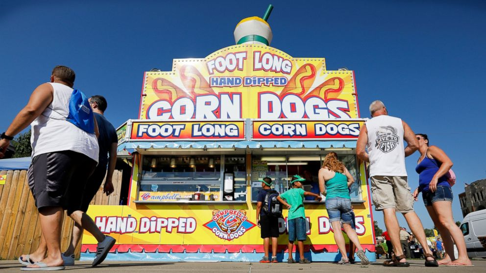 FILE - In this Aug. 9, 2018 file photo, Iowa State fairgoers line up to get a corn dog at a concession stand during the opening day of the Iowa State Fair in Des Moines, Iowa. The Iowa State Fair has confirmed that it will require all food and drink