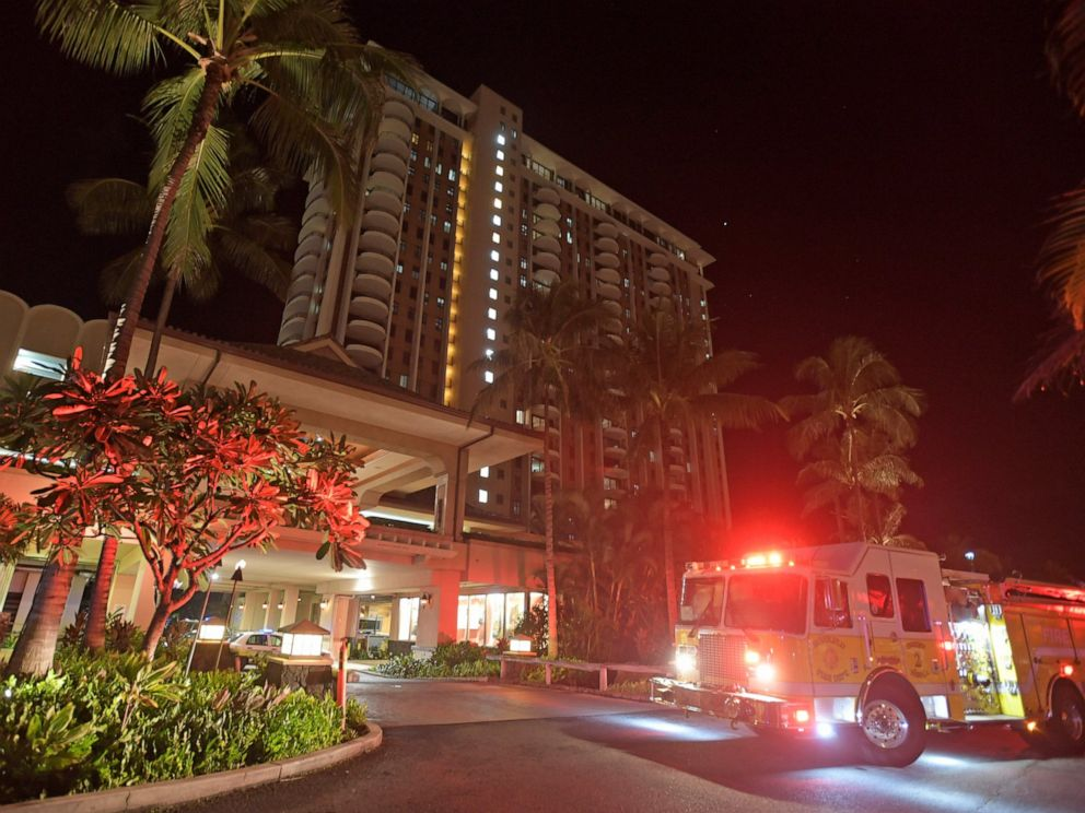 In this Tuesday, Aug. 6, 2019, photo, first responders from Honolulu Fire Department and Honolulu Police Department arrive at the Grand Waikikian in response to a fire reported on the 28th floor, in Honolulu. (Bruce Asato/Honolulu Star-Advertiser via AP)