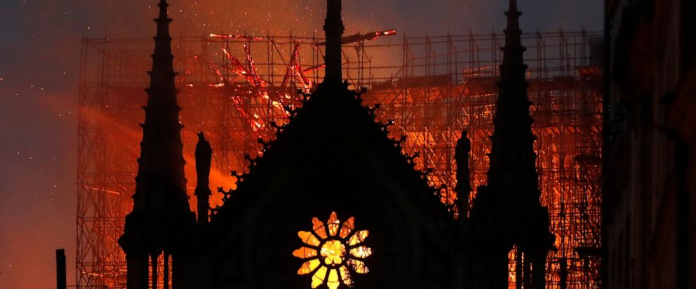 Flames and smoke rise from Notre Dame cathedral as it burns in Paris, Monday, April 15, 2019. Massive plumes of yellow brown smoke is filling the air above Notre Dame Cathedral and ash is falling on tourists and others around the island that marks th