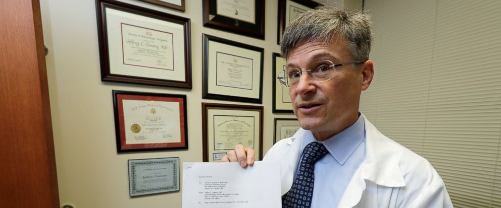 In this Dec. 20, 2018, photo, Dr. Jeffrey Clemons, a pelvic reconstructive surgeon, poses for a photo in Tacoma, Wash., with a letter to state Attorney General Bob Ferguson that he helped draft and was signed by more than 60 Washington state surgeons