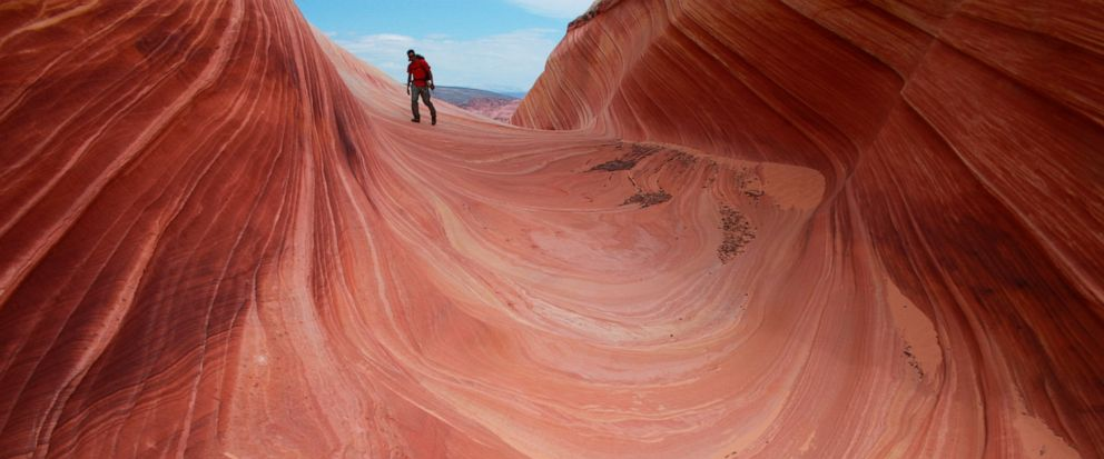FILE - This May 28, 2013 file photo shows a on a rock formation known as The Wave in the Vermilion Cliffs National Monument in Arizona. A new proposal could mean bigger crowds at one of the most exclusive hiking spots in the southwestern United State
