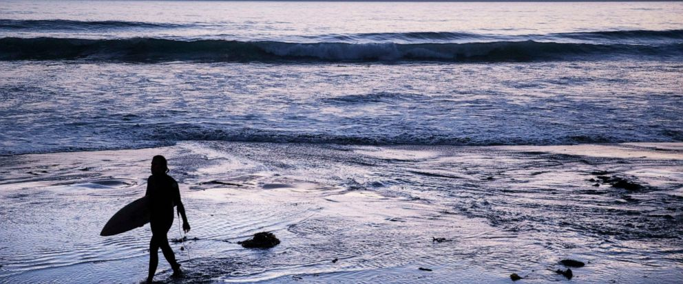 FILE - In this July 2, 2019, file photo a surfer walks out of the water after riding waves at dusk at Scripps Beach in San Diego. With hotel and airline loyalty programs, you can take the sting out of this year's travel costs by leveraging those expe