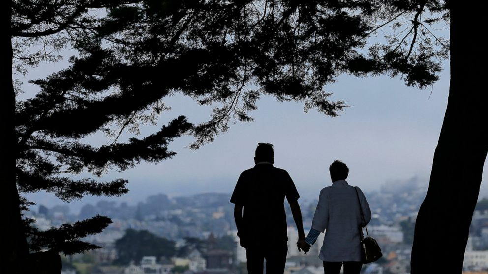 FILE- In this July 3, 2017, file photo a man and woman walk under trees down a path at Alta Plaza Park in San Francisco. Looking at the income, living expenses and life spans of today's retirees can help you make the right financial moves so your golden years aren't tarnished by an unexpected shortfall. (AP Photo/Jeff Chiu, File)
