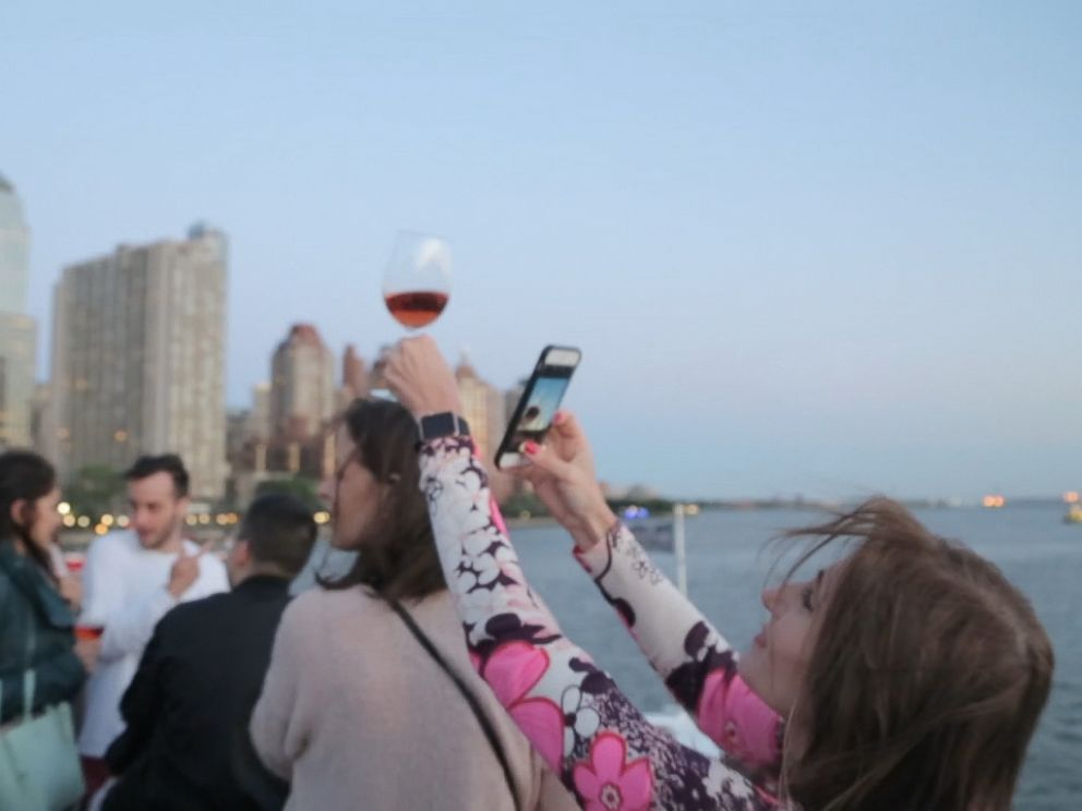A guest at the La Nuit en Rosé festival in New York City snaps a photo of her glass of Rosé.