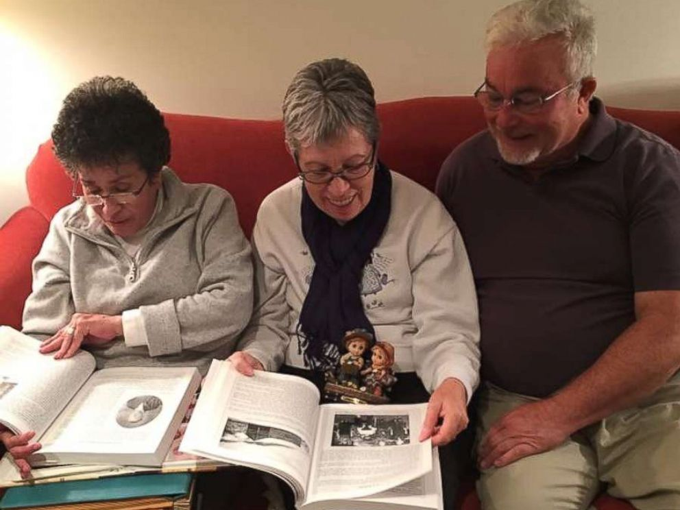 PHOTO: Siblings Sylvia Faison Graves Kewer, Billy Lee Ray, and Nancy Goode ODonnell look at an old photo album on Nov. 12, 2017.