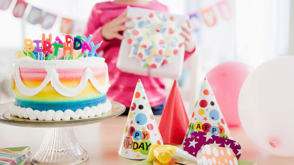 A girl holds a gift at birthday party in this undated stock photo.