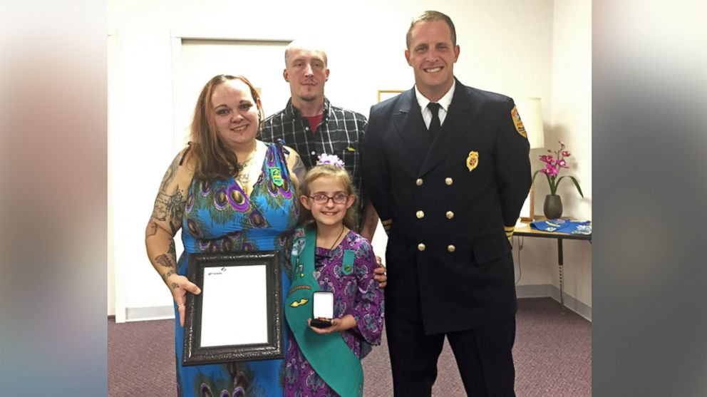 Alexandria, Indiana, Fire Chief Brian Cuneo poses with Melina Lakey, 9, and her parents, Ashley McCollum-Lakey and Jeff Lakey.