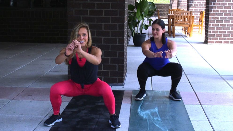 PHOTO: NYC fitness trainer, Jennifer Amoroso shows Dani Kipp how to do a sumo squat jump.