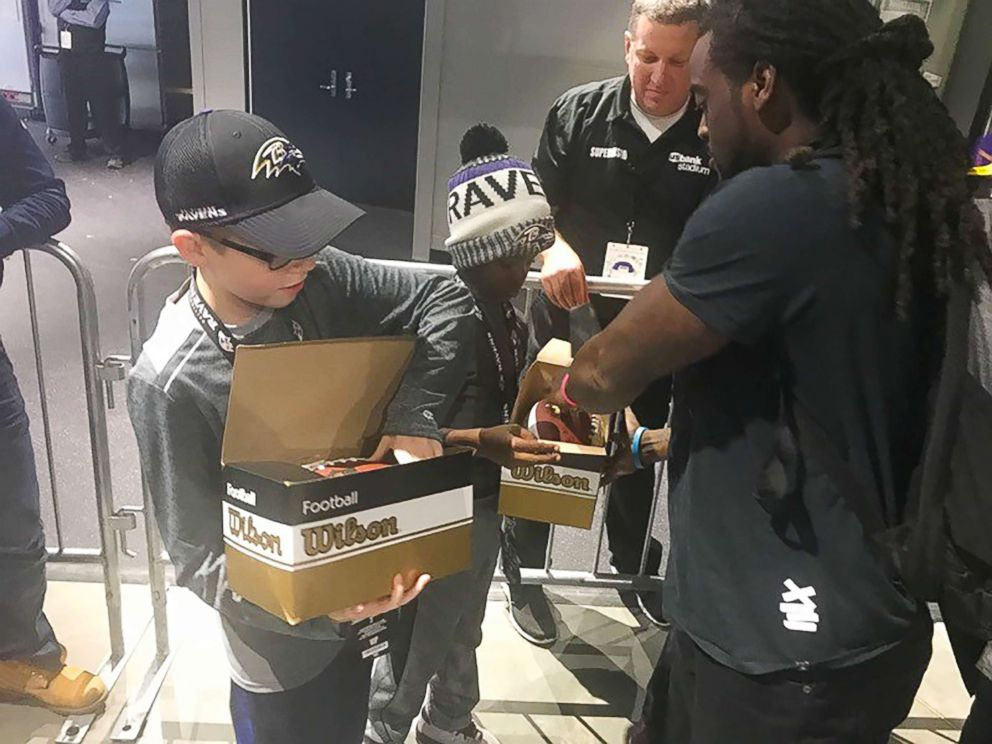 PHOTO: Baltimore Ravens star Alex Collins gives autographed footballs to Carl Tubbs, 12, and Miles Tubbs, 10.